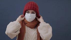 Το άρρωστο κορίτσι βάζει σε μια μάσκα βήχει και λυπημένος φιλμ μικρού μήκους