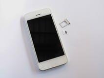 Το άσπρο έξυπνο τηλέφωνο, sim λαναρίζει το δίσκο και το μικρό έγγραφο που μιμούνται ως α Στοκ Εικόνες
