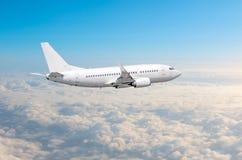 Το άσπρο αεροπλάνο πετά το ύψος, επίπεδο πτήσης υψηλό στον ουρανό επάνω από το μπλε ουρανό σύννεφων Στοκ εικόνες με δικαίωμα ελεύθερης χρήσης
