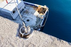 Το άσπρο αλιευτικό σκάφος είναι δεμένο με το σχοινί για το δαχτυλίδι χάλυβα στην αποβάθρα, Στοκ φωτογραφία με δικαίωμα ελεύθερης χρήσης