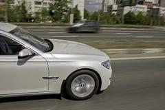 Το άσπρο αυτοκίνητο πηγαίνει γρήγορα στην πόλη στοκ εικόνα