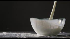 Το άσπρο γάλα χύνεται σε ένα κύπελλο γυαλιού σε ένα μαύρο υπόβαθρο Ο παφλασμός γάλακτος μειώνεται από το κύπελλο στον γκρίζο πίνα απόθεμα βίντεο