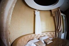 Το άσπρο γαμήλιο φόρεμα κρεμά σε ένα όμορφο εσωτερικό Στοκ εικόνα με δικαίωμα ελεύθερης χρήσης