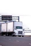 Το άσπρο ημι φορτηγό με δύο ρυμουλκά παραδίδει το φορτίο στην εθνική οδό Στοκ Εικόνα