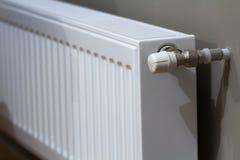 Το άσπρο θερμαντικό σώμα θέρμανσης με τη βαλβίδα θερμοστατών στον τοίχο σε ένα εσωτερικό διαμερισμάτων μετά από την ανακαίνιση λε Στοκ φωτογραφία με δικαίωμα ελεύθερης χρήσης