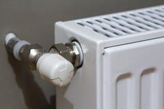 Το άσπρο θερμαντικό σώμα θέρμανσης με τη βαλβίδα θερμοστατών στον τοίχο σε ένα εσωτερικό διαμερισμάτων μετά από την ανακαίνιση λε Στοκ φωτογραφίες με δικαίωμα ελεύθερης χρήσης
