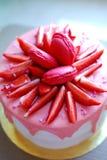 Το άσπρο κέικ με τις ρόδινες σταλαγματιές διακόσμησε με τα macarons, φράουλες και ψεκάζει στο χρυσό πίνακα κέικ Στοκ φωτογραφίες με δικαίωμα ελεύθερης χρήσης
