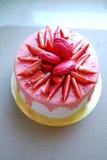 Το άσπρο κέικ με τις ρόδινες σταλαγματιές διακόσμησε με τα macarons, φράουλες και ψεκάζει στο χρυσό πίνακα κέικ στοκ φωτογραφία
