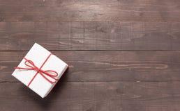 Το άσπρο και κόκκινο κιβώτιο δώρων είναι στο ξύλινο υπόβαθρο με την κενή SP Στοκ Εικόνες