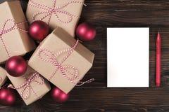Το άσπρο κενό φύλλο με τα χριστουγεννιάτικα δώρα στην ξύλινη τοπ άποψη υποβάθρου, επίπεδη βάζει Κατάλογος δώρων Χριστουγέννων, έν Στοκ Φωτογραφία