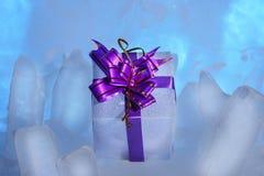το άσπρο κιβώτιο δώρων με ένα όμορφο πορφυρό τόξο βρίσκεται στον μπλε πάγο Στοκ φωτογραφία με δικαίωμα ελεύθερης χρήσης