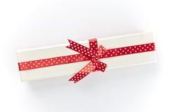 Το άσπρο κιβώτιο με μια κόκκινα κορδέλλα και ένα τόξο Στοκ Εικόνες