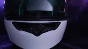 Το άσπρο κράνος πλήρης-προσώπου μοτοσικλετών περιστρέφεται στο μαύρο υπόβαθρο απόθεμα βίντεο