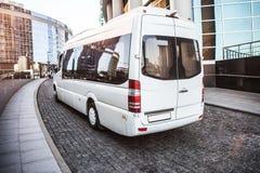 Το άσπρο μίνι λεωφορείο κινείται κάτω από την οδό στοκ φωτογραφία
