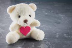 Το άσπρο παιχνίδι teddy αφορά με την καρδιά ένα γκρίζο υπόβαθρο Το σύμβολο Στοκ φωτογραφία με δικαίωμα ελεύθερης χρήσης