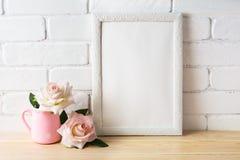 Το άσπρο πρότυπο πλαισίων με δύο χλωμιάζει - ρόδινα τριαντάφυλλα Στοκ Φωτογραφίες