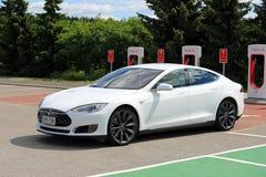 Το άσπρο πρότυπο S ηλεκτρικό αυτοκίνητο τέσλα αφήνει το σταθμό χρέωσης Στοκ φωτογραφίες με δικαίωμα ελεύθερης χρήσης