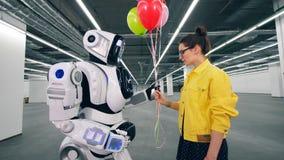 Το άσπρο ρομπότ παίρνει μια δέσμη των μπαλονιών από τα χέρια ενός κοριτσιού απόθεμα βίντεο