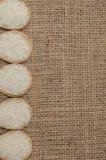 Το άσπρο ρύζι στο κύπελλο μπαμπού στην τσάντα σάκων για το κείμενο υποβάθρου Στοκ Εικόνες
