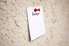 το άσπρο σημειωματάριο με τις λέξεις φορά ` τ ξεχνά Στοκ φωτογραφία με δικαίωμα ελεύθερης χρήσης