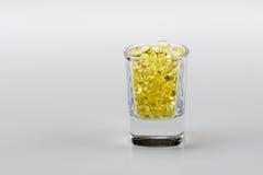 Το άσπρο υπόβαθρο καψών χαπιών βιταμινών Ε στην πυροβοληθείσα σφιχτή άποψη γυαλιού κλείνει τη συγκομιδή Στοκ Εικόνα