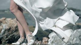 Το άσπρο ύφασμα κυματίζει στον αέρα, παφλασμός πτώσεων νερού στα πόδια του κοριτσιού στο άσπρο φόρεμα φιλμ μικρού μήκους