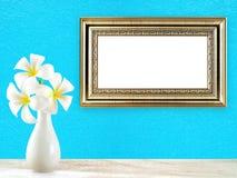Το άσπρο plumeria ανθίζει στο άσπρο κεραμικό βάζο στο ξύλινο πάτωμα και το χρυσό εκλεκτής ποιότητας πλαίσιο εικόνων στο μπλε υπόβ Στοκ εικόνα με δικαίωμα ελεύθερης χρήσης