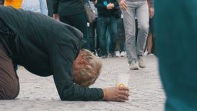 Το άστεγο άτομο επαιτών με το πλαστικό φλυτζάνι στα χέρια του στο πεζοδρόμιο ικετεύει για τις ελεημοσύνες από τους ανθρώπους που  απόθεμα βίντεο