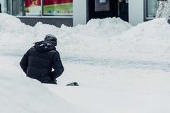 Το άστεγο άτομο ικετεύει για τα γόνατα ελεημοσυνών στο χιόνι στοκ εικόνες