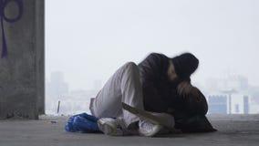 Το άστεγο άτομο πηγαίνει στον ύπνο στην τσάντα απορριμάτων, αστικό υπόβαθρο φιλμ μικρού μήκους