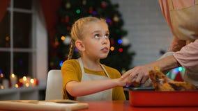 Το άτακτο κορίτσι θέλει να αγγίξει το πικάντικο ψημένο κοτόπουλο, το grandma δεν επιτρέπει, Χριστούγεννα απόθεμα βίντεο