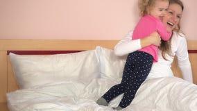 Το άτακτο μικρό κορίτσι ήρθε στο κρεβάτι και αγκαλιάζει τη μητέρα της Τα καλά οικογενειακά κορίτσια έχουν τη διασκέδαση φιλμ μικρού μήκους