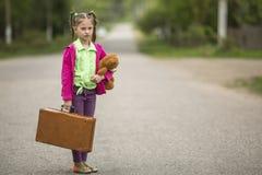 Το άτακτο μικρό κορίτσι με μια βαλίτσα και ένα Teddy αντέχουν πηγαίνουν σε ένα ταξίδι Ταξίδι Στοκ εικόνα με δικαίωμα ελεύθερης χρήσης