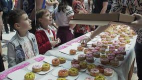 Το άτομο έβαλε ζωηρόχρωμα doughnuts στον πίνακα στο εμπορικό κέντρο δίκαιος άνθρωποι Παιδιά φιλμ μικρού μήκους