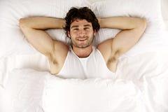 Το άτομο έβαλε στο άσπρο κρεβάτι εξετάζοντας επάνω το χαμόγελο καμερών Στοκ Εικόνα
