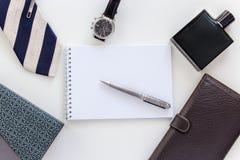Το άτομο έθεσε: ρολόι, δεσμός, συνδετήρας δεσμών, μάνδρα, άρωμα, πορτοφόλι και σημειωματάριο στοκ εικόνα