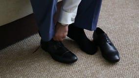 Το άτομο δένει τα μαύρα παπούτσια του απόθεμα βίντεο