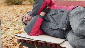 Το άτομο έντυσε στα παλαιά ενδύματα που κοιμούνται στον πάγκο στο πάρκο με το άστεγο σημάδι βοήθειας φιλμ μικρού μήκους