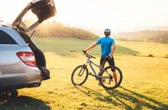 Το άτομο ήρθε με το αυτοκίνητο στο βουνό με το ποδήλατό του το παίρνει μακριά και μένοντας και απολαμβάνοντας το τοπίο Biking εικ στοκ φωτογραφία με δικαίωμα ελεύθερης χρήσης