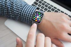 Το άτομο δίνει το έξυπνο ρολόι αφής με τα εικονίδια εγχώριας οθόνης apps Στοκ φωτογραφία με δικαίωμα ελεύθερης χρήσης