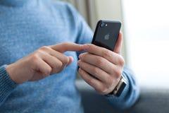 Το άτομο δίνει το iPhone 7 εκμετάλλευσης ρολογιών της Apple αεριωθούμενο μαύρο Onyx Στοκ Φωτογραφία