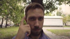 Το άτομο αγγίζει το ναό του με το δάχτυλό του απόθεμα βίντεο
