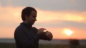 Το άτομο αγγίζει το smartwatch Όμορφο ηλιοβασίλεμα στο υπόβαθρο απόθεμα βίντεο