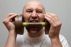 Το άτομο δαγκώνει τα δόντια του σε έναν αλτήρα σιδήρου Στοκ Εικόνες