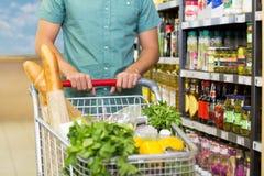 Το άτομο αγοράζει τα προϊόντα με το καροτσάκι του Στοκ φωτογραφία με δικαίωμα ελεύθερης χρήσης