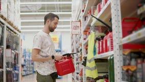 Το άτομο αγοράζει τη νέα κόκκινη δεξαμενή για τα καύσιμα αυτοκινήτων απόθεμα βίντεο