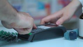 Το άτομο αγοράζει το φάρμακο με το τερματικό καρτών στο φαρμακείο Pos τερματικό στο ιατρικό κατάστημα απόθεμα βίντεο