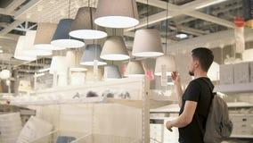 Το άτομο αγοραστών εξετάζει την κατάταξη lampshade στο μεγάλο λιανικό κατάστημα απόθεμα βίντεο
