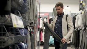 Το άτομο αγοραστών προσέχει ένα γκρι hoody σε ένα κατάστημα με τα αθλητικά ενδύματα φιλμ μικρού μήκους