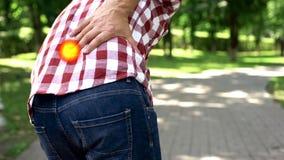 Το άτομο αισθάνεται τον αιχμηρό πόνο στην πλάτη στο πάρκο, χαλασμένοι νωτιαίοι δίσκοι, το σημείο δείχνει τον πόνο στοκ εικόνα με δικαίωμα ελεύθερης χρήσης